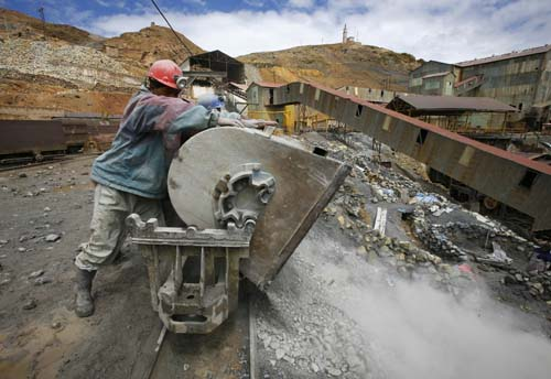 A Bolivian miner empties a rail car outside the Pailaviri mine in the Cerro Rico mountain in Potosi