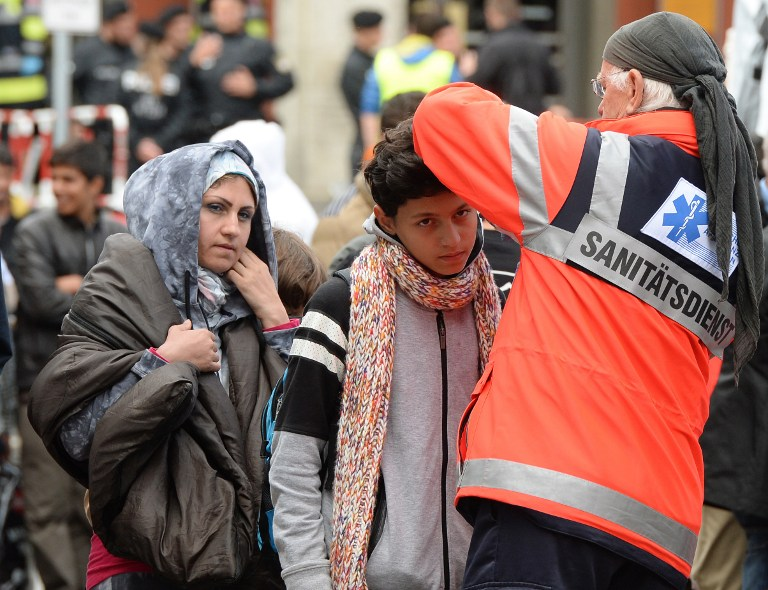 "Medical staff checks migrants after their arrival at the main railway station in Munich, southern Germany, on September 06, 2015. Germany on Sunday prepared for more refugees to arrive from Hungary via Austria, a day after thousands were greeted, often by volunteers holding signs that read ""Welcome to Germany"". But calls grew for a European solution to its worst refugee crisis since World War II. AFP PHOTO / CHRISTOF STACHE"