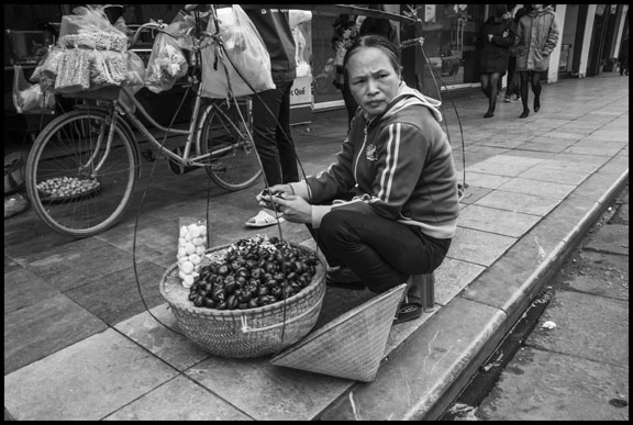 HANOI, VIETNAM - 09DECEMBER15 - A streetseller sells chestnuts on the street in Hanoi.  Copyright David Bacon