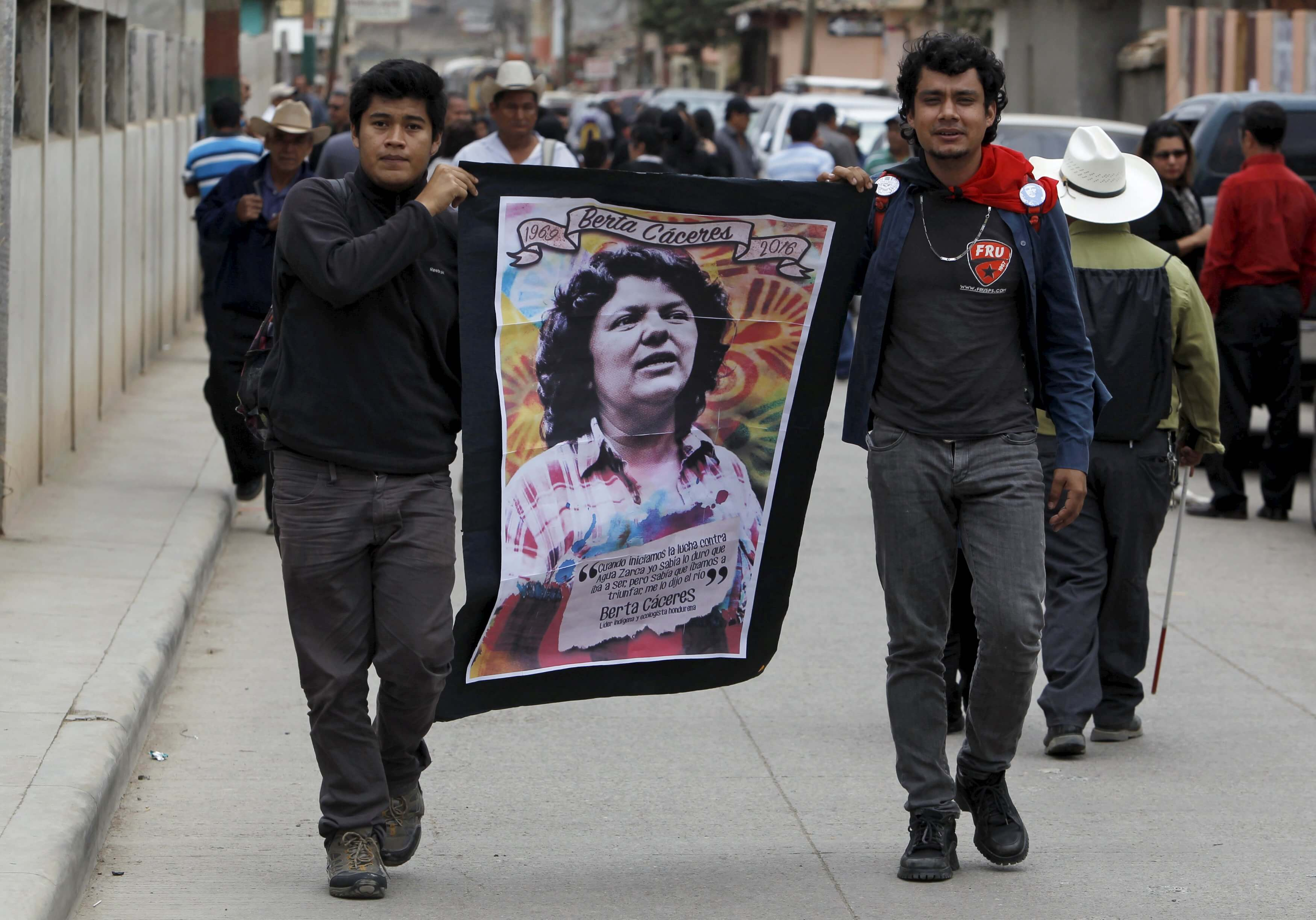 Supporters carry a banner with an image of slain environmental rights activist Berta Caceres along a street during her funeral in the town of La Esperanza, outside Tegucigalpa