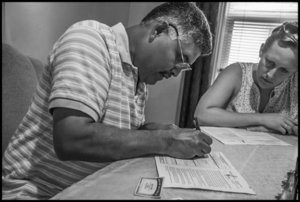 NEBRASKA CITY, NE - 22SEPTEMBER16 - Isidro Rojas Garcia, an immigrant construction worker from Mexico, registers to vote for the first time after having been a U.S. citizen for 16 years.  Helping him is Abby Kretz, an organizer from the Heartland Workers Center.  Copyright David Bacon