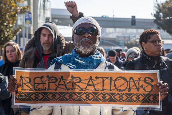 SAN FRANCISCO, CA - 16JANUARY17 - March celebrating the birthday of Rev. Martin Luther King Jr.  Reparations refers to the demand that the Uniited States make reparations to African Americans for 400 years of slavery.  Copyright David Bacon