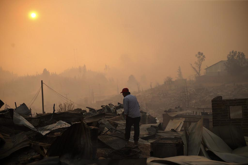 A man stands amid the remains of a burnt down house after a forest fire devastated Santa Olga, 240 kilometres south of Santiago, on January 26, 2017.  Six people -- among them four firefighters and two police -- have now been killed battling vast forest fires in central Chile, officials said Wednesday. Multiple blazes have ravaged 238,000 hectares (588,000 acres) and are growing, the National Forestry Corporation said in a statement. / AFP PHOTO / PABLO VERA LISPERGUER