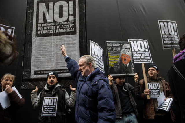 NEW YORK, NY - JANUARY 11: A man holding up his right arm walks past a small group of anti-Donald Trump across the street from Trump Tower, January 11, 2017 in New York City. On Wednesday morning, Trump is having his first press conference since winning the election.   Drew Angerer/Getty Images/AFP
