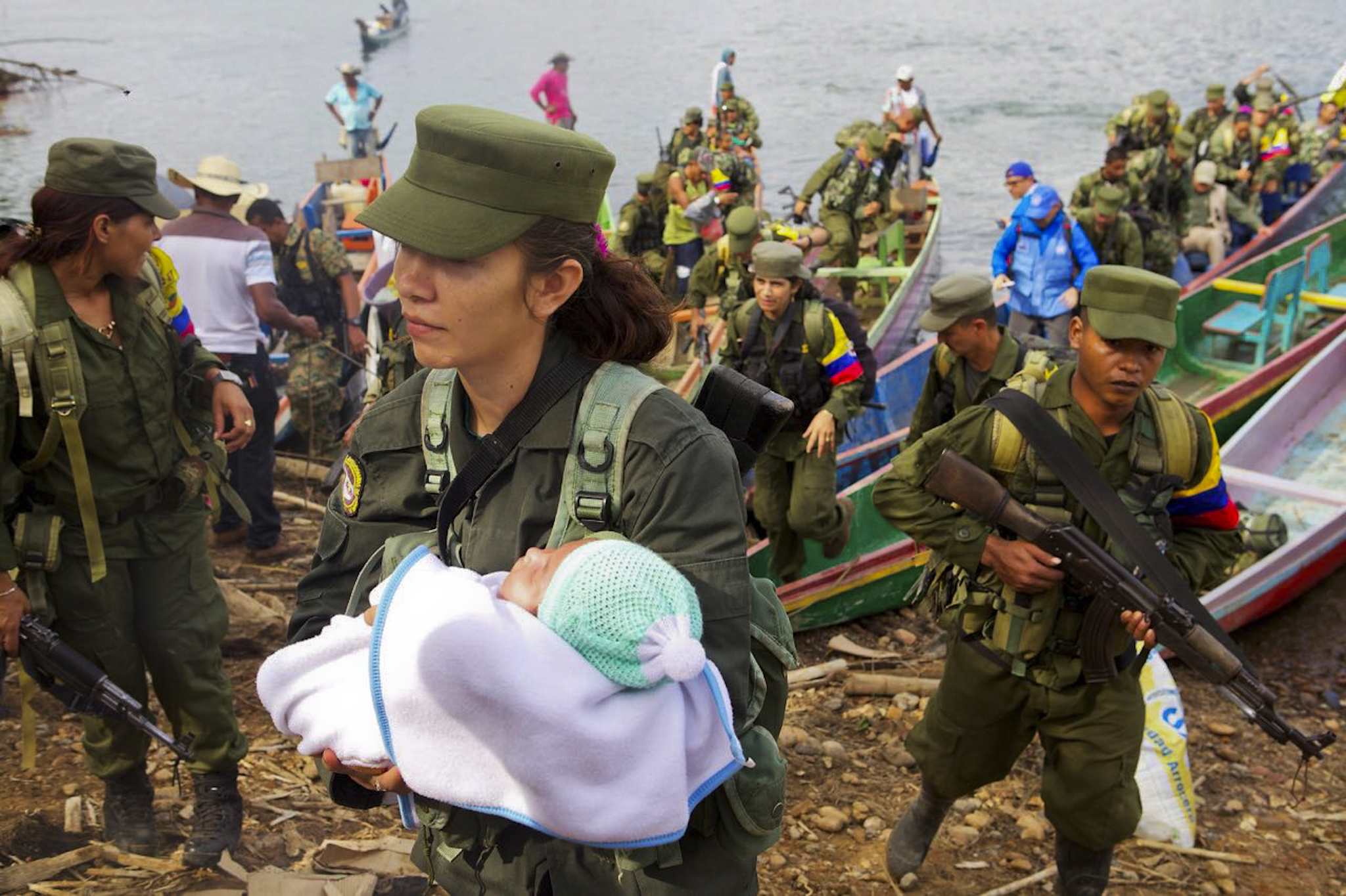 A female guerrilla in full combat gear and holding her child arrives with her comrades in arms to hand on their weapons in the remote area of  El Gallo, near the Urra reservoir, Cordoba department, northeastern Colombia on February 1, 2017.  Colombia's FARC rebels gathered in demobilization zones on Wednesday to start a historic disarmament process to end Latin America's last major armed conflict. / AFP / JESUS COLOADO   COLOMBIA-FARC-PEACE-DEMOBILIZATION