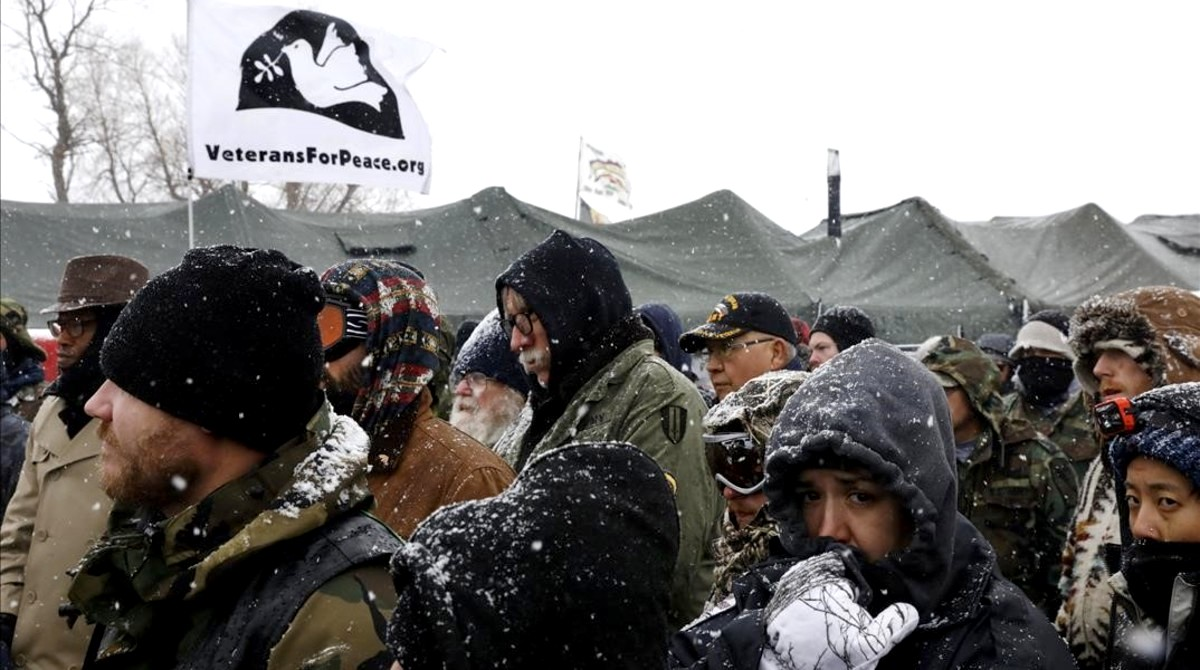 Veterans gather for a briefing inside of the Oceti Sakowin camp during a snow fall as  water protectors  continue to demonstrate