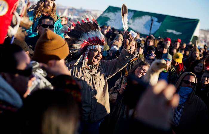 Una multitud celebra en el campamento Oceti Sakowin el anuncio de que el Cuerpo de Ingenieros del Ejército de Estados Unidos no concederá una servidumbre para el oleoducto Dakota Access en Cannon Ball, North Dakota, el domingo 4 de diciembre de 2016. (AP Foto/David Goldman)