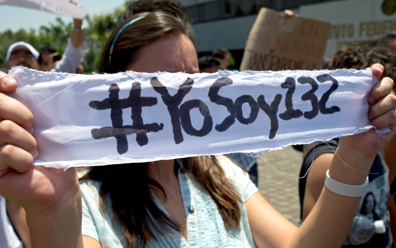 """A Mexican university student, member of the new movement called """"Yo soy 132"""" (I Am #132), holds a banner inside the Mexican Electoral Institute offices on May 31, 2012 in Mexico City. The students handed a petition to Electoral authorities, asking for an additional television debate among the four presidential candidates. Mexico will hold presidential elections next July 1st. AFP PHOTO/Omar Torres        (Photo credit should read OMAR TORRES/AFP/GettyImages)"""