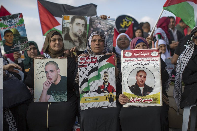 epa05942284 Palestinian family members and activists holding pictures of relatives in Israeli prisons, hold a solidarity rally at Nelson Mandela square in the West Bank town of Ramallah, 03 May 2017. More than 1,200 of the 6,500 Palestinian prisoners in Israel, have been on a hunger strike for 17 days. The strike is being held to highlight poor living conditions at Israeli prisons.  EPA/ATEF SAFADI (Newscom TagID: epalivetwo685365.jpg) [Photo via Newscom]