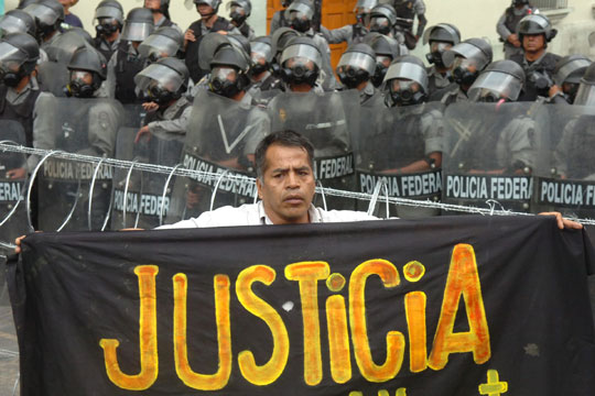 manifestante_posa_pancarta_pidiendo_justicia_oaxaca