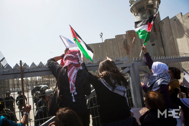 Palestinian women try to climb over a fence during a demonstration against the occupation one day before the international women day,at Qalandiya checkpoint, West Bank, March 7, 2015. The annual march was repressed by the Israeli army.