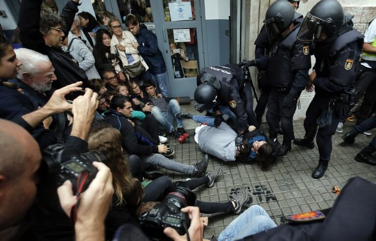 Spanish police officers immobilize some people outside a polling station in Barcelona, on October 1, 2017, on the day of a referendum on independence for Catalonia banned by Madrid.  More than 5.3 million Catalans are called today to vote in a referendum on independence, surrounded by uncertainty over the intention of Spanish institutions to prevent this plebiscite banned by justice.  / AFP PHOTO / PAU BARRENA