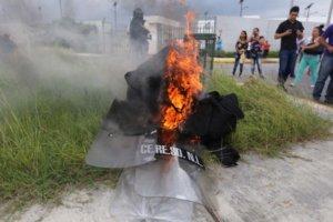 (171010) -- CADEREYTA, octubre 10, 2017 (Xinhua) -- Personas caminan frente a equipo policial en llamas en las afueras la c·rcel de Cadereyta, luego de que se registrara un motÌn, en Cadereyta, estado de Nuevo LeÛn, MÈxico, el 10 de octubre de 2017. Un motÌn de reos que durÛ varias horas en la c·rcel de Cadereyta, estado mexicano de Nuevo LeÛn, dejÛ el martes un saldo de dos policÌas y seis presos lesionados, informÛ el gobierno estatal. (Xinhua/Str) (da) (dp)
