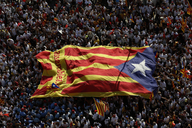 """People carry a giant """"estelada"""" flag, a symbol of Catalonian pro-independence, during a demonstration calling for the independence of Catalonia in Barcelona. Spain's main banking associations warned Friday that a victory for Catalonia's secession drive would create severe banking problems for the new Mediterranean nation left outside the European Union."""