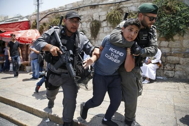 Israeli border guards detain a Palestinian youth during a demonstration outside the Lions Gate, a main entrance to Al-Aqsa mosque compound, due to newly-implemented security measures by Israeli authorities which include metal detectors and cameras, in Jerusalem's Old City on July 17, 2017. Israel reopened the ultra-sensitive holy site, after it was closed following an attack by Arab Israeli men in which two Israeli policemen were killed. / AFP PHOTO / AHMAD GHARABLI